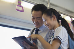 观看在地铁的微笑的父亲和女儿一部电影在数字式片剂 图库摄影
