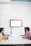 观看在墙壁上的电视的商人在创造性的办公室 图库摄影