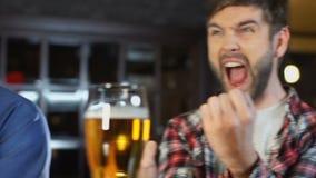 观看在大屏幕上的三个多种族朋友体育比赛在啤酒客栈,支持 股票视频