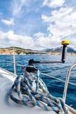 观看在小船的板料绞盘在海岸线的背景 免版税库存照片
