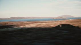 观看在山和水,湖美好的日落风景里面汽车  外面车阴影的看法 股票录像