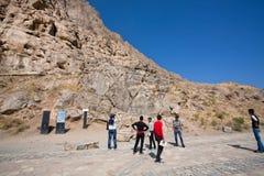 观看在岩石的小组游人巨型的赫拉克勒斯雕象 图库摄影