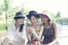 观看在巧妙的电话屏幕上的小组年轻亚裔妇女朋友 免版税库存照片