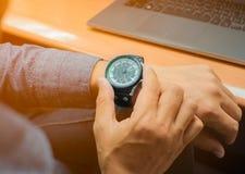 观看在手上被佩带的手表的人 库存图片