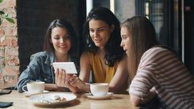 观看在智能手机屏幕上的愉快的年轻人滑稽的内容在咖啡馆笑 股票录像