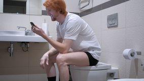 观看在智能手机的愉快的人,坐在洗手间洗脸台 库存照片