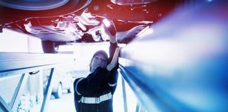 观看在有光的一辆汽车下的技工女孩 免版税库存照片