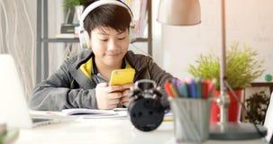 观看在有微笑面孔的手机的亚裔男孩 库存图片