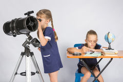 观看在望远镜的女孩天体,另一个女孩等待观察的结果 库存图片