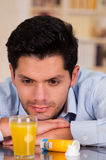 观看在杯的英俊的人冒泡片剂水 免版税图库摄影