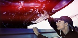 观看在汽车下的技工女孩 免版税库存图片