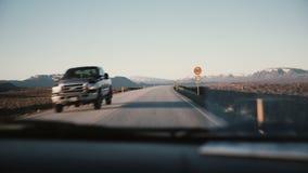 观看在汽车里面通过在美丽的乡下路用美好的日落,山的挡风玻璃环境美化 股票视频