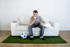 观看在沙发的足球迷电视比赛有草的投地毯我 免版税库存照片