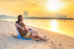观看在海滩的夫妇浪漫日出 库存照片