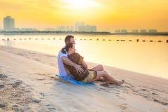 观看在海滩的夫妇浪漫日出 免版税库存图片