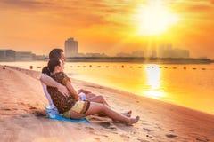 观看在海滩的夫妇浪漫日出 免版税库存照片