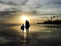 观看在海滩的家庭剪影日出 免版税图库摄影