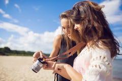 观看在照相机的两个女性朋友照片在海滩 免版税库存照片