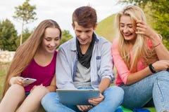 观看在片剂个人计算机的三个朋友滑稽的电影在公园 免版税库存图片
