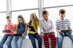观看在片剂屏幕上的小组好奇孩子材料 免版税图库摄影