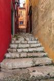 观看在狭窄的街道的台阶在新的红色和破旧的ye之间 免版税图库摄影
