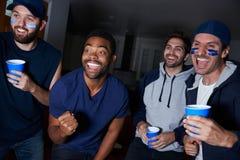 观看在电视上的小组男性体育迷比赛 免版税库存照片