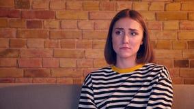 观看在电视几乎哭泣的开会的年轻俏丽的女孩特写镜头画象一部哀伤的电影在一栋舒适公寓的长沙发 影视素材