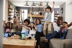观看在电视和欢呼上的两个家庭体育 免版税库存图片