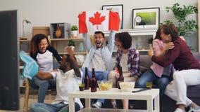 观看在电视欢呼的挥动的旗子做的快乐的加拿大人体育高五 股票录像