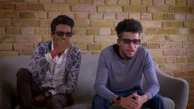 观看在电视的两个年轻男性朋友特写镜头射击一3D恐怖电影一起坐长沙发户内在舒适 影视素材