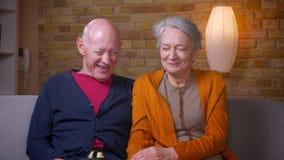 观看在电视的喜剧电影笑对泪花的资深白种人配偶在客厅在沙发 影视素材