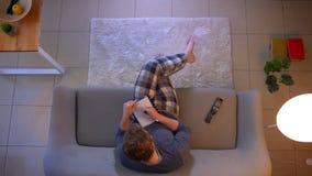 观看在电视的年轻便服男性特写镜头顶面射击一个烹调展示坐地板和写下 股票录像