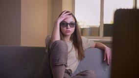 观看在电视的年轻可爱的白种人女性特写镜头画象一3D恐怖电影坐长沙发户内  股票视频