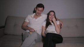 观看在电视的愉快的夫妇一部电影在家坐长沙发和吃玉米花 股票视频