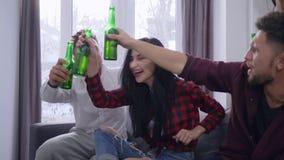 观看在电视的朋友活比赛与兴奋坐长沙发,叫喊和做与啤酒瓶的他们多士在 股票录像