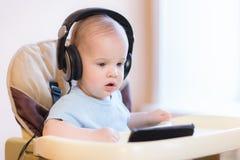 观看在电话的小孩一部动画片 库存图片