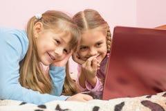 观看在膝上型计算机的一部动画片和嘲笑滑稽的片刻的姐妹 免版税库存照片