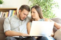 观看在膝上型计算机的线内容的乏味男朋友 免版税库存图片