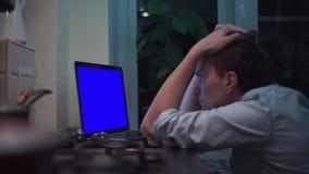 观看在蓝色关键笔记本计算机显示的人在厨房在火炉附近 影视素材