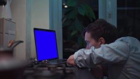 观看在蓝色关键笔记本计算机显示的人在厨房在火炉附近 股票录像