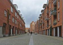 观看在鹅卵石街道下用露台的房子用在双方的红砖墙壁 免版税库存照片