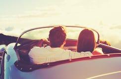 观看在经典葡萄酒汽车的夫妇日落 免版税库存图片