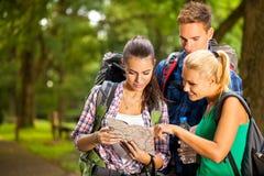 观看地图的三个远足者 免版税库存图片