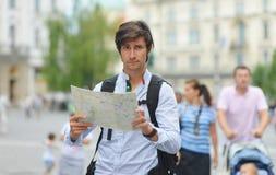 观看地图的年轻游人 库存图片