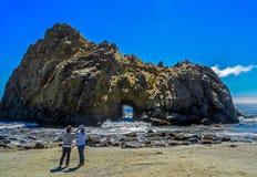 观看大瑟尔岩层的游人在太平洋 免版税库存照片