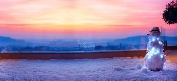 观看太阳的逗人喜爱的雪人在屋顶大阳台去下来 免版税库存图片