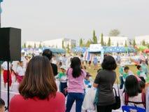 观看她的孩子的亚裔母亲参加体育天事件在学校 免版税库存图片