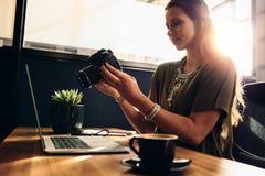 观看她的照相机的年轻女性vlogger,当编辑她的vlog时 免版税库存图片