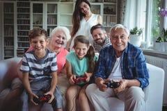 观看孩子的家庭打电子游戏 免版税库存图片