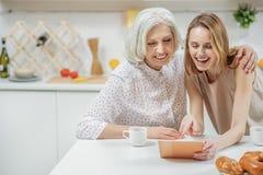 观看家庭照片的快乐的妇女 免版税库存图片